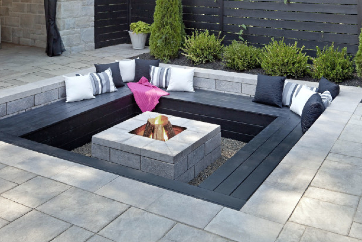 modern outdoor fire pits - black builtin bench around a modern stone fire pit (source pm homedesigns)